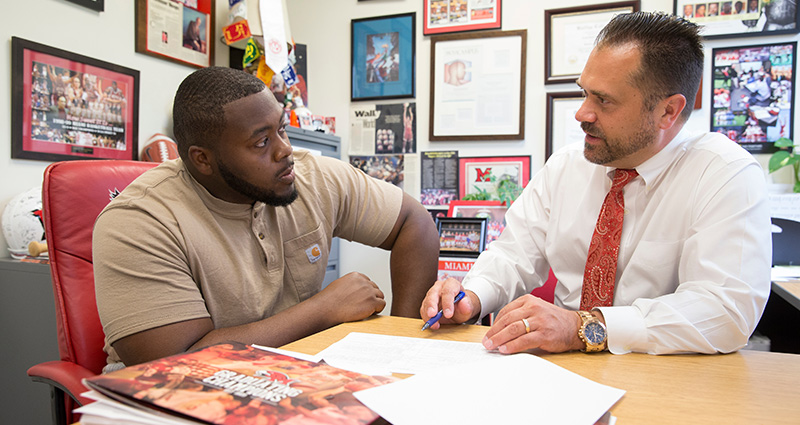 Defensive tackle Nate Trawick, a junior economics major and marketing minor, talks to Craig Bennett, assistant athletic director for academic support services.